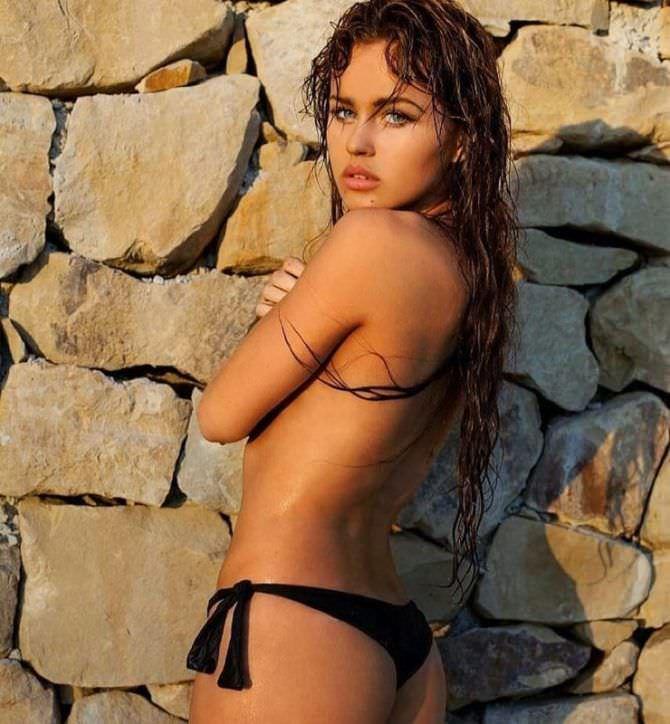 Рози Мак фото возле каменной стены