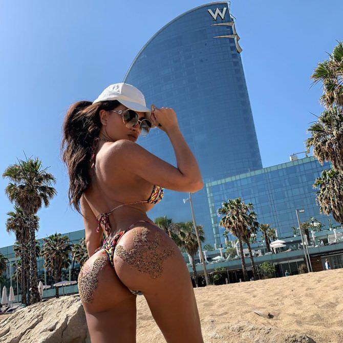 Тучи Кэш фотография на пляже в бикини и кепке